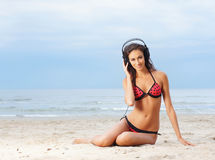 A young woman listening to the music on the beach Royalty Free Stock Photo