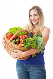 Young healthy beautiful woman with a basket full of fresh vegeta Stock Image