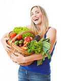 Young healthy beautiful woman with a basket full of fresh vegeta Royalty Free Stock Image
