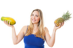 Young healthy beautiful woman with a pineapple and a papaya Royalty Free Stock Images