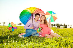 Young healthy beauty pregnant woman with her husband and rainbow Stock Photos