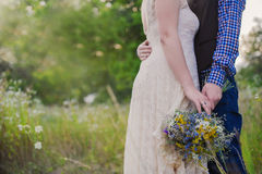 Young healthy couple fashionable girl in a wedding dress guy in a plaid shirt standing with a bouquet of bright flowers in hands, Stock Image