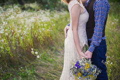 Young healthy couple fashionable girl in a wedding dress guy in a plaid shirt standing with a bouquet of bright flowers in hands, Stock Photos