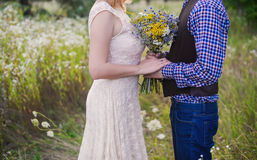 Young healthy couple fashionable girl in a wedding dress guy in a plaid shirt standing with a bouquet of bright flowers in hands, Royalty Free Stock Photos