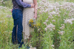 Young healthy couple fashionable girl in a wedding dress guy in a plaid shirt standing with a bouquet of bright flowers in hands, Stock Photography