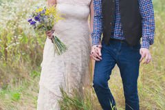Young healthy couple fashionable girl in a wedding dress guy in a plaid shirt standing with a bouquet of bright flowers in hands, Royalty Free Stock Images
