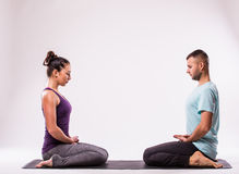 Young healthy couple in yoga position Royalty Free Stock Photos