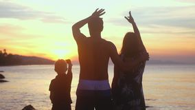 Young healthy family on summer vacations waves hands at sunset sunshine on tropical beach. Slow motion. 3840x2160. Young healthy family on summer vacations waves stock footage