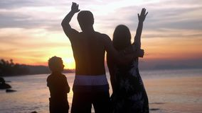 Young happy family hugging on summer vacations and waving their hands at beautiful sunset on tropical beach. Slow motion. Young healthy family on summer stock video footage
