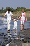Young, Healthy Family Walking Along A Sunny Beach Stock Photography