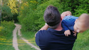 A young healthy father walks with his son in the park. Carries a baby in his arms, rear view stock video footage