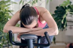 Young healthy fit woman training at home on exercise bike during work-out feeling exhausted and dizzy, lowered his head on his han Royalty Free Stock Image