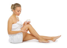 Young healthy girl applying body cream isolated Stock Photography
