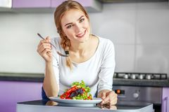 A young healthy girl eats a vegetable salad. Woman in white clot royalty free stock photo