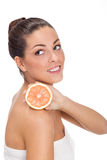 Young healthy girl holding an half orange on the shoulder Stock Photos