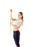 Young healthy girl with a perfect figure with measuring tape, is Royalty Free Stock Photo