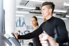 Young healthy group of people working out on a elliptic trainer. In a fitness center Royalty Free Stock Photos