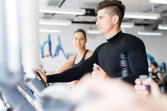 Young healthy group of people working out on a elliptic trainer. In a fitness center Royalty Free Stock Images