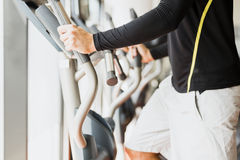 Young healthy group of people working out on a elliptic trainer. In a fitness center Royalty Free Stock Photo