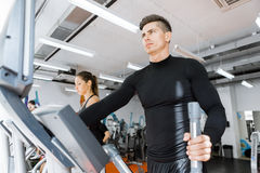 Young healthy group of people working out on a elliptic trainer. In a fitness center Royalty Free Stock Photography