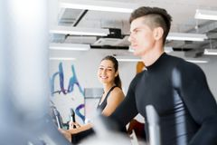 Young healthy group of people working out on a elliptic trainer. In a fitness center Stock Photos