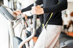 Young healthy group of people working out on a elliptic trainer. In a fitness center Royalty Free Stock Image