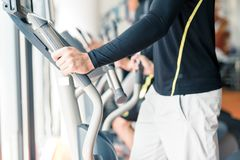 Young healthy group of people working out on a elliptic trainer. In a fitness center Stock Images