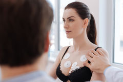 Young healthy lady taking part in medical experiment. As a volunteer. Pretty attractive athletic women helping cardiologist conducting a study on heart stock photo