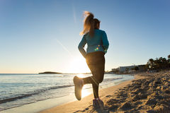 Young healthy lifestyle fitness woman running at sunrise beach.  Royalty Free Stock Photo