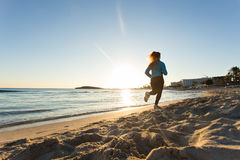 Young healthy lifestyle fitness woman running at sunrise beach.  Stock Photos