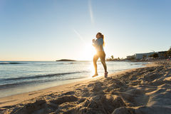 Young healthy lifestyle fitness woman running at sunrise beach.  Royalty Free Stock Photography