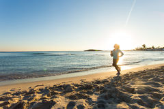 Young healthy lifestyle fitness woman running at sunrise beach.  Royalty Free Stock Images