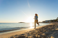 Young healthy lifestyle fitness woman running at sunrise beach.  Royalty Free Stock Image