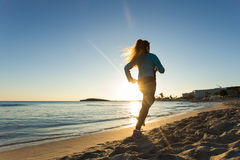 Young healthy lifestyle fitness woman running at sunrise beach.  Stock Photography