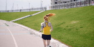 Young healthy lifestyle woman running at sunrise road. Royalty Free Stock Images