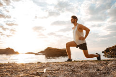Young healthy man athlete doing squats at the beach Stock Images