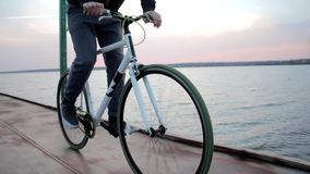 Young healthy man bikes on road in pink evening sunset near calm river landscape stock footage