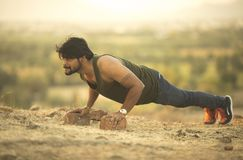 Young Healthy Man. Closeup portrait, young healthy handsome man performing pushup outside at mountain stock images