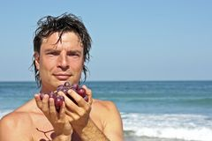 Young healthy man eating grapes Stock Images
