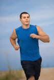 Young Healthy Man Jogging by Beach Stock Image