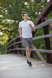 Young Healthy Man Jogging Cross Bridge Royalty Free Stock Images