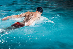 Young healthy man with muscular body swims. In swimming pool Royalty Free Stock Image
