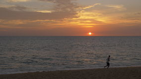 Running Sunset. A young man wearing shorts and a white tanktop is running / jogging on a beautiful, tropical paradise beach at sunset. Running from left to right stock footage