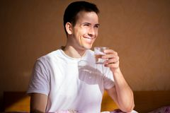 Young healthy man stretching after sleep with glass of water, drink every day. Concept of healthy habits Royalty Free Stock Photos