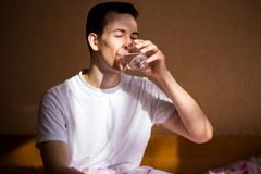 Young healthy man stretching after sleep with glass of water, drink every day. Concept of healthy habits Royalty Free Stock Images