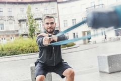 Man strengthening his arms in the city. Royalty Free Stock Images