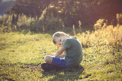 Young healthy smiling little child is sitting on the grass in pa Stock Photos