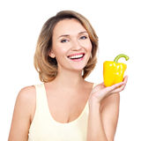 Young healthy smiling woman holds pepper. Royalty Free Stock Image