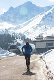Young healthy sport man running on asphalt road at snow mountains in trail runner hard workout in energy and endurance. Concept with a beautiful cold winter stock image
