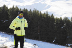 Young healthy sport man running in snow mountains in trail runner hard  workout in winter Royalty Free Stock Photography